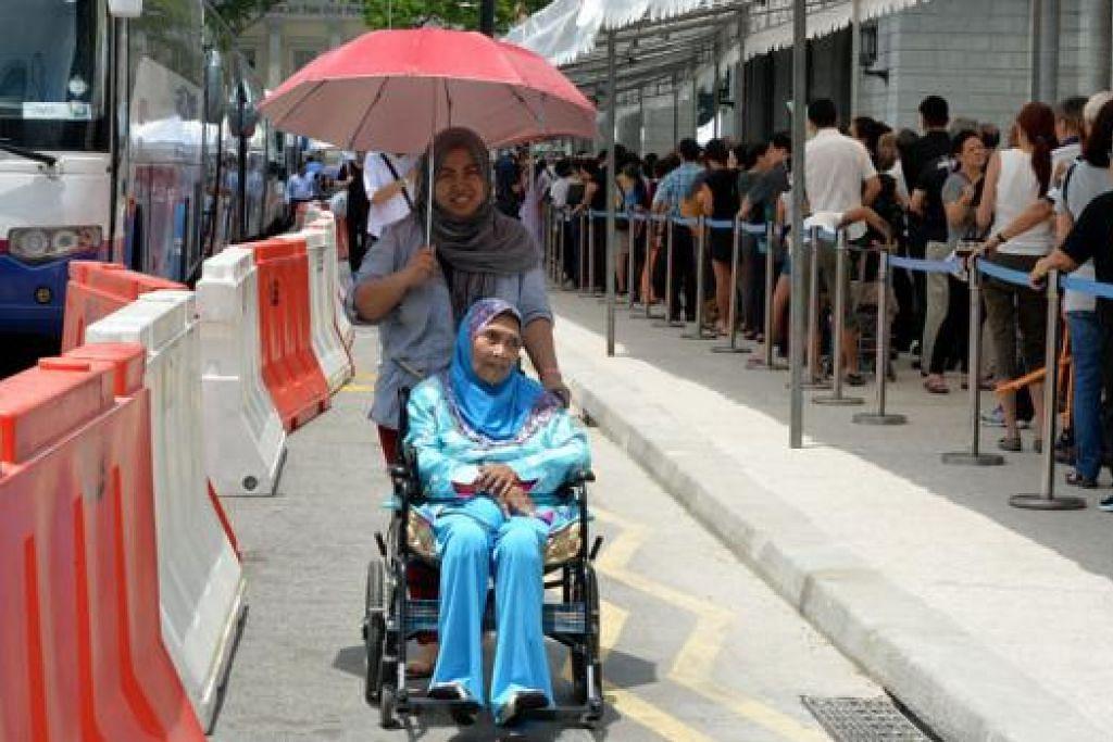 KUATKAN DIRI UNTUK MENDIANG ENCIK LEE: Meskipun berkerusi roda dan tidak begitu sihat, Cik Fatimah Abdul Bakar, 70 tahun, menggagahkan diri datang bersama pembantunya Cik Suriati untuk memberi penghormatan kepada mendiang Encik Lee. – Foto M.O. SALLEH