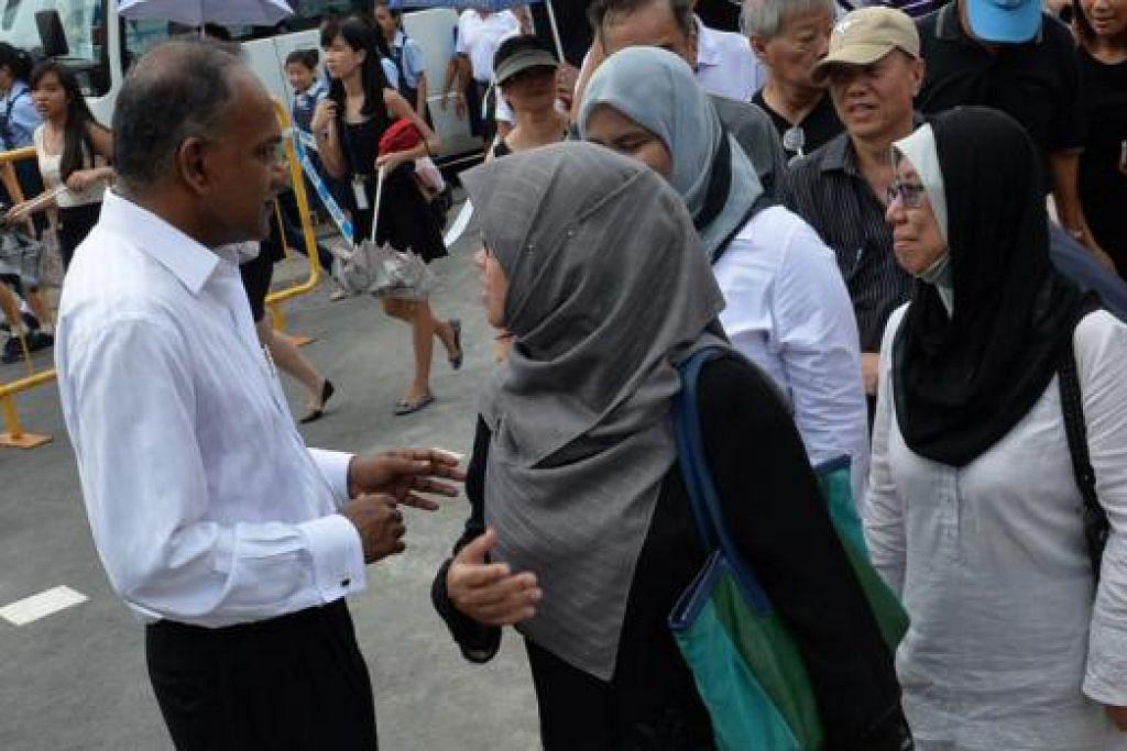 'TURUN PADANG': Menteri Ehwal Luar merangkap Undang-Undang, Encik K Shanmugam, menyapa orang ramai yang beratur untuk memberi penghormatan kepada mendiang Encik Lee. – Foto  M.O. SALLEH