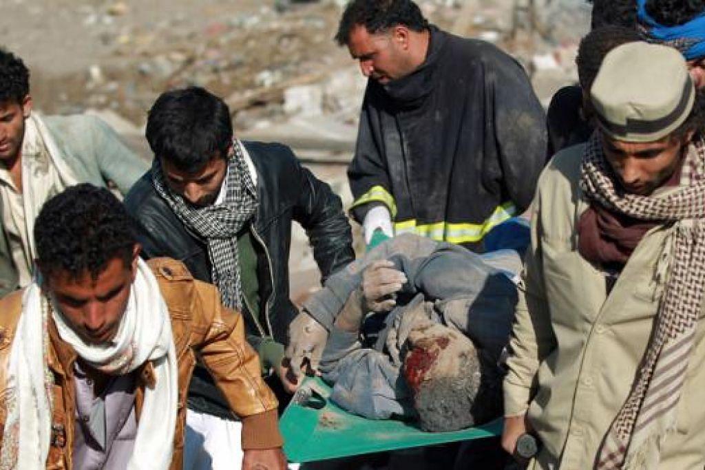 BANTUAN PERUBATAN: Penduduk Yaman memgusung mangsa selepas berjaya mengeluarkannya daripada runtuhan bangunan yang musnah selepas serangan udara Arab Saudi semalam. - Foto AFP