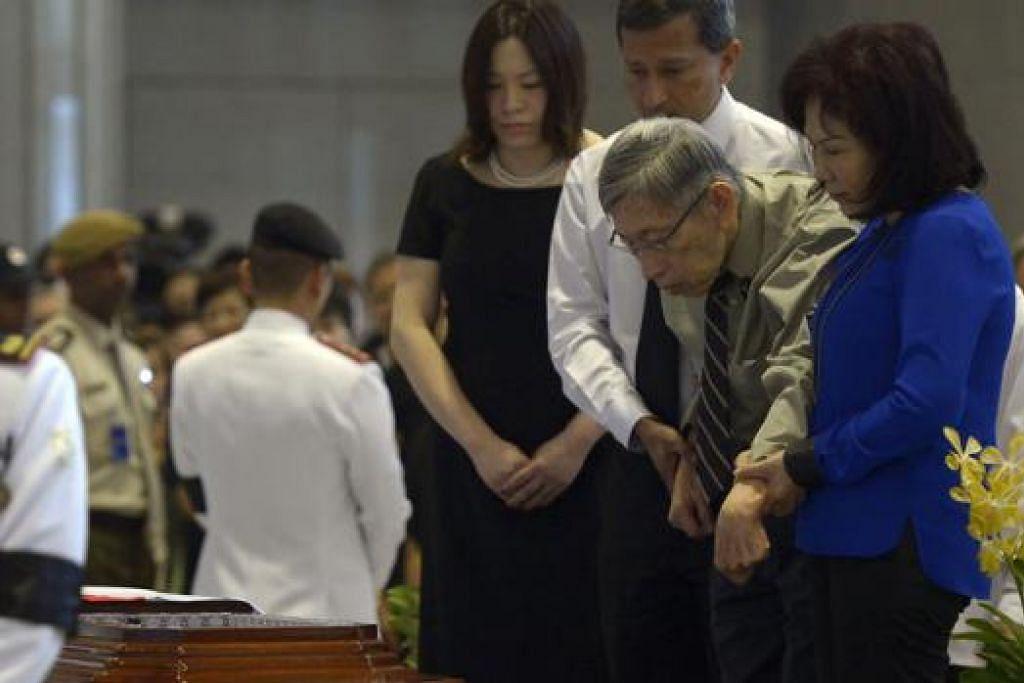 PENGHORMATAN DARI 'LAWAN': AP pembangkang paling lama berkhidmat, Encik Chiam See Tong (berbaju hijau), yang dipapah Dr Vivian Balakrishnan, memberi penghormatan terakhir kepada mendiang Encik Lee di Bangunan Parlimen semalam. Beliau ditemani isterinya, Cik Lina Chiam (kanan), yang juga Anggota Parlimen Tanpa Kawasan Undi (NCMP), serta anak mereka, Cik Camilla. - Foto THE STRAITS TIMES