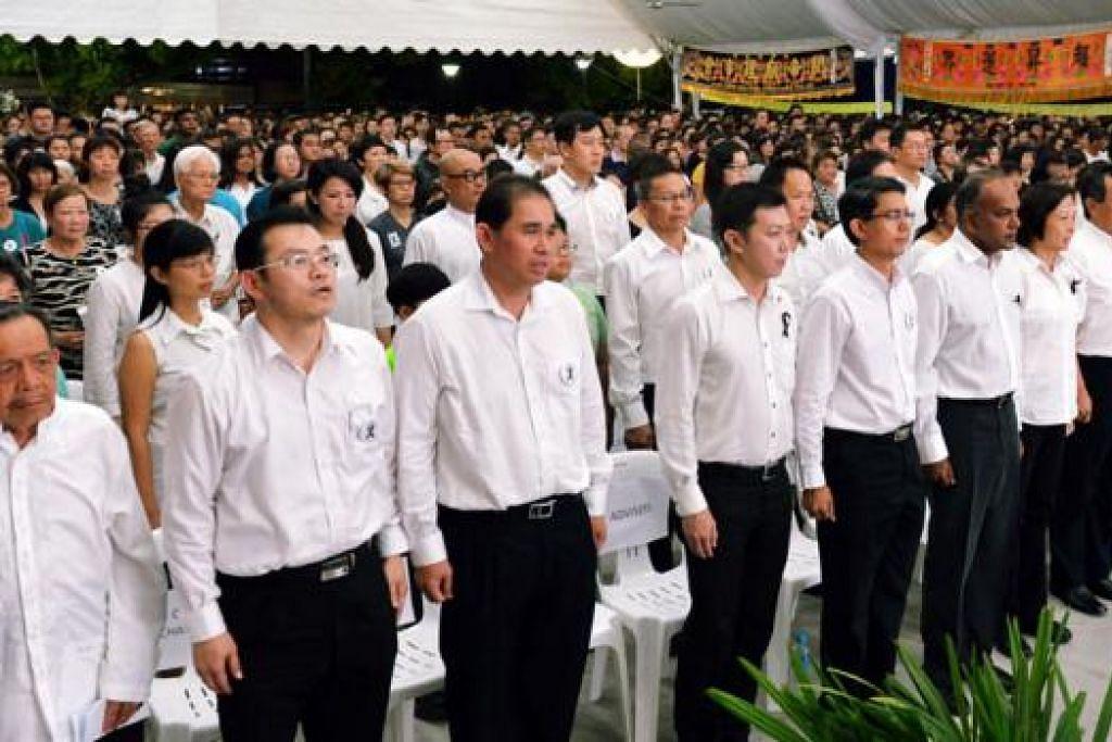 SERTAI PENDUDUK HARGAI SUMBANGAN: Encik Shanmugam (empat dari kanan) menyertai penduduk dalam upacara memperingati Encik Lee Kuan Yew di kawasan undi Nee Soon. - Foto KHALID BABA