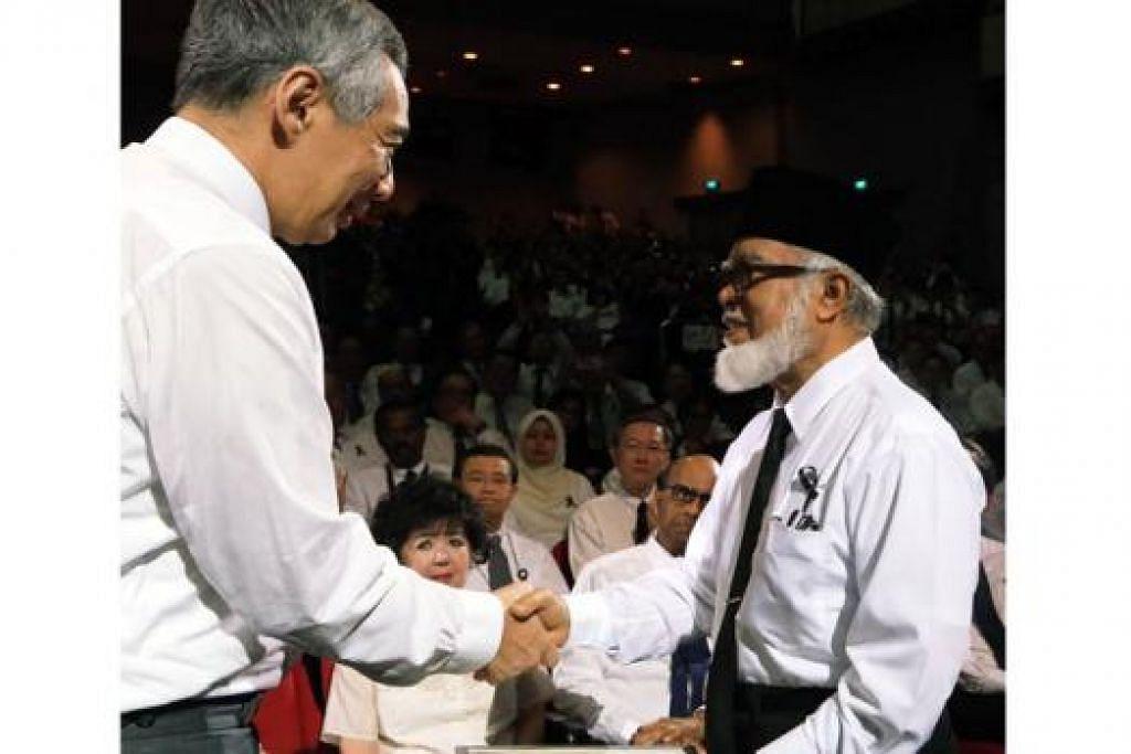 TAKZIAH KEPADA PM LEE: Shaikh Syed Isa Semait memberi surat takziah kepada Perdana Menteri Lee Hsien Loong semasa satu majlis memberi penghormatan kepada mendiang Encik Lee semalam. - Foto-foto KHALID BABA