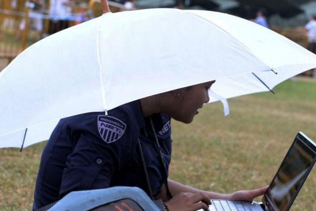 TERUS BERTUGAS: Seorang wartawan dari laman televisyen dalam talian, Net, yang berpangkalan di Indonesia, terus bekerja di atas sebuah kerusi di Padang dengan berpayung semasa hujan gerimis semalam. - Foto TAUFIK A. KADER