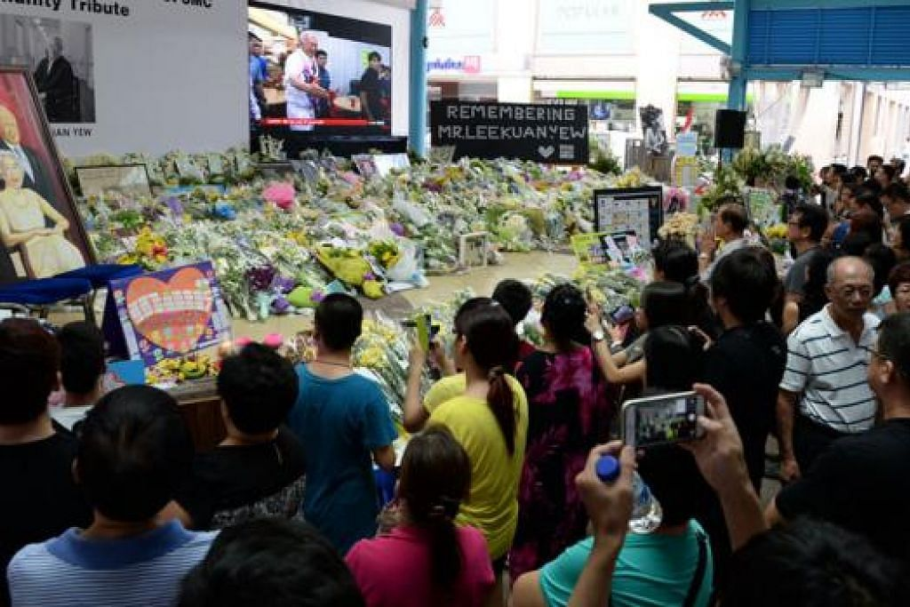 BANJIRAN MANUSIA: Begini keadaan di salah satu tapak masyarakat di Ang Mo Kio Central Stage @ Ang Mo Kio Town Centre yang dipenuhi penduduk setempat yang berpusu-pusu memberikan penghormatan mereka, termasuk Encik Hamzah yang memperingati mendiang Encik Lee menerusi daya kreatifnya ini. - Foto-foto ZAINAL YAHYA