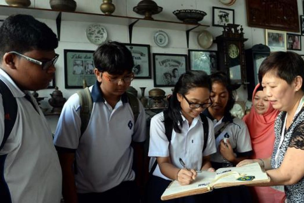 TINGGALKAN PESANAN: Nurul Hannah menulis pesanannya di buku pengunjung bekas studio Malay Film Productions (MFP) sambil diperhatikan (dari kanan) pemandu 'Jejak Balestier', Cik Belinda Mock, Cik Massuniza dan pelajar Siti Nur Farzana, Muhammad Haziq dan Ameer Abbas.