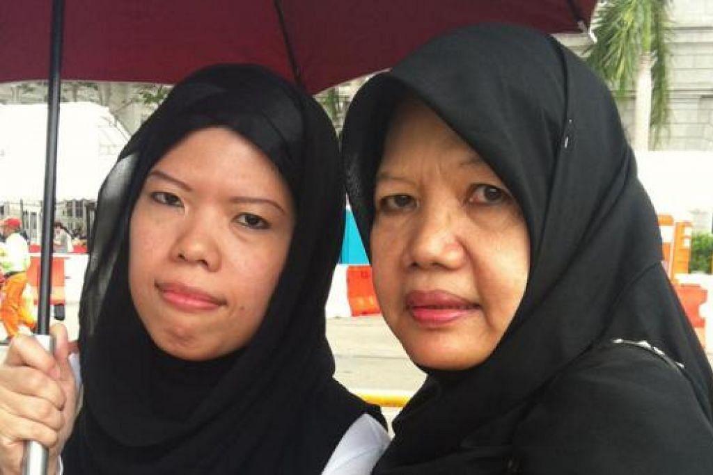TIDAK PUTUS ASA: Pasangan ibu dan anak, (dari kiri) Cik Shirin Hoe, 34 tahun, dan ibunya, Cik Sapiah Rosdi, 62 tahun, kembali beratur di Padang buat kali kedua untuk memberi penghormatan terakhir kepada mendiang Encik Lee. - Foto NURMAYA ALIAS