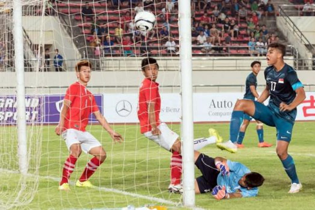 GOL SESIA: Irfan, (jersi biru, paling kanan) menyumbat gol dalam babak pertama, tetapi ia tidak diambil kira kerana pengadil mendakwa beliau telah mengasari penjaga gawang Laos. - Foto PERSATUAN BOLA SEPAK SINGAPURA