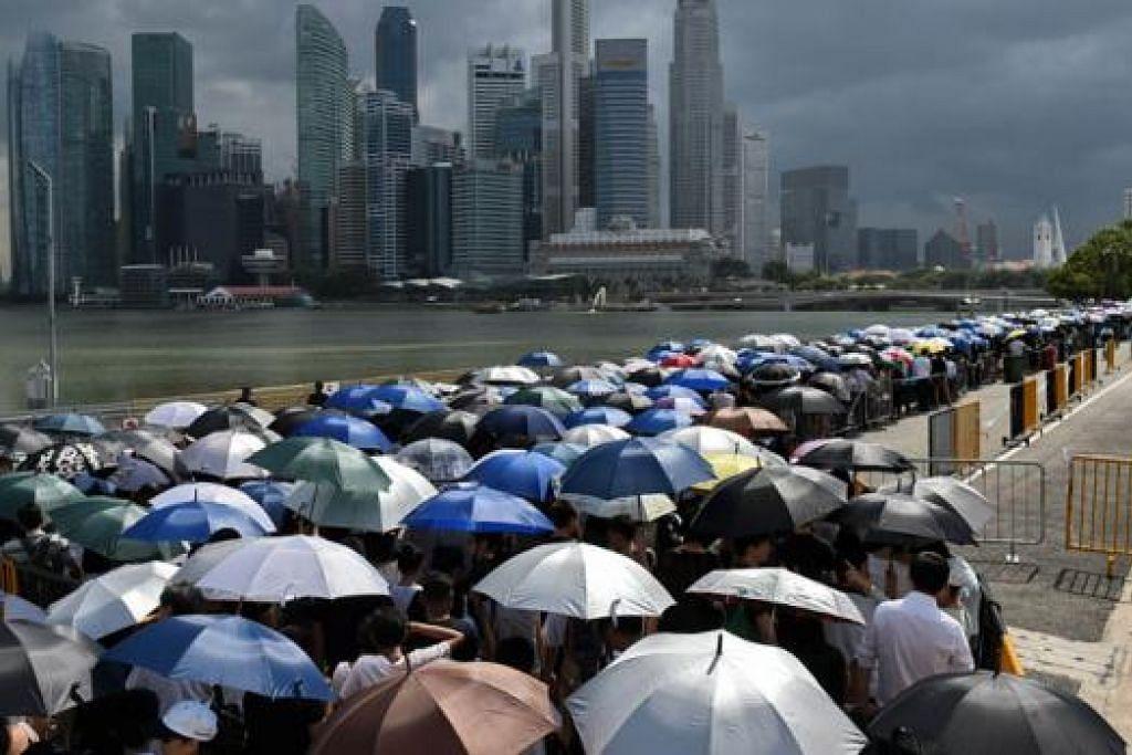 DEMI PEMIMPIN TERSAYANG: Tanpa mengira panas mahupun hujan, rakyat sanggup beratur sehingga 10 jam untuk memasuki Bangunan Parlimen bagi memberikan penghormatan terakhir kepada mendiang Encik Lee. - Foto AFP