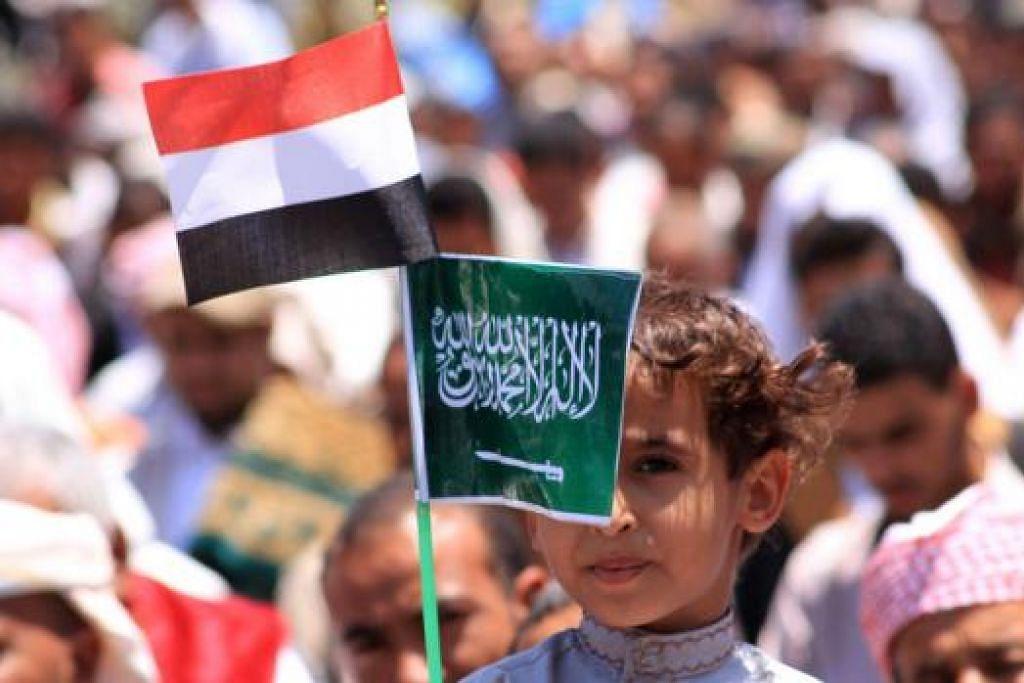 LAHIRKAN SOKONGAN: Seorang kanak-kanak Yaman memegang bendera Arab Saudi (kanan) dan bendera Yaman dalam perhimpunan di Taez bagi menyokong operasi ketenteraan Arab Saudi di Yaman. - Foto AFP
