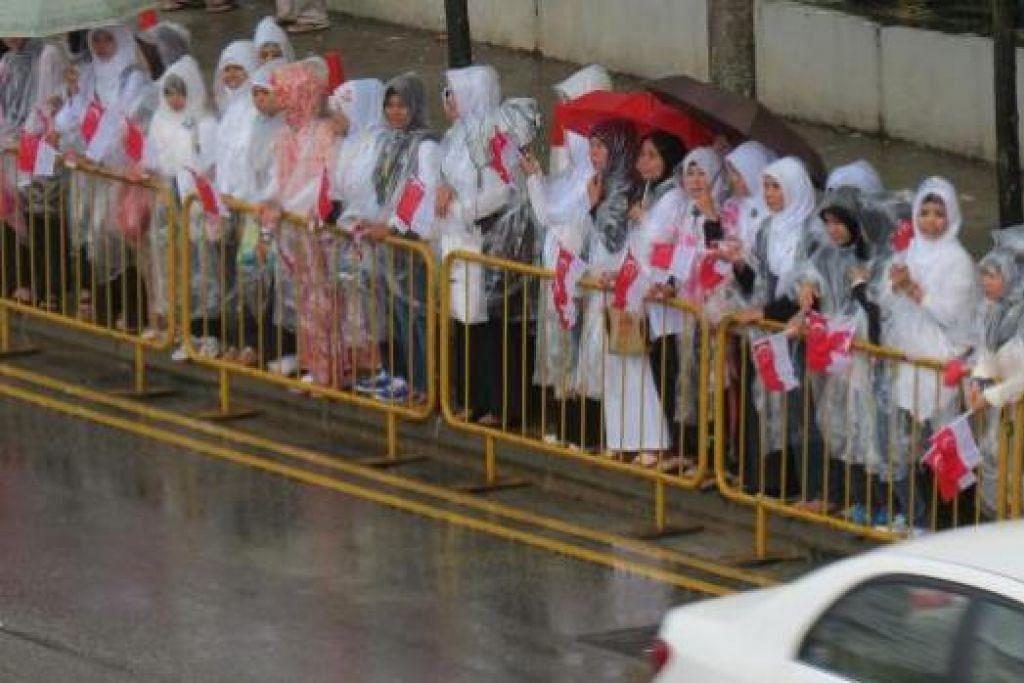BERMANDI HUJAN: Warga dengan payung dan baju hujan berdiri di pinggir jalan, menanti ketibaan perarakan jenazah Perdana Menteri Pengasas Lee Kuan Yew. - Foto MASJID MUJAHIDIN
