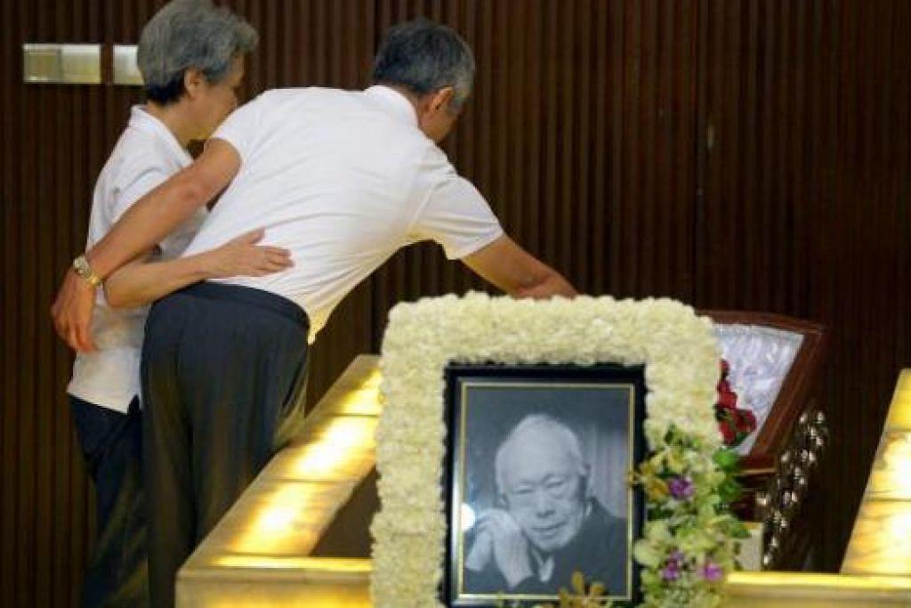 SELAMAT BERPISAH 'PAPA': Perdana Menteri, Encik Lee Hsien Loong, meletakkan sekuntum bunga mawar ke dalam keranda bapanya, mendiang Encik Lee Kuan Yew, sebelum keranda diusung bagi pembakaran mayat. Beliau didakap isterinya, Cik Ho Ching. - Foto THE STRAITS TIMES