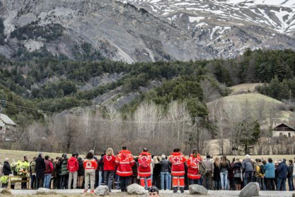 BERI PENGHORMATAN: Penduduk kawasan Seyne di Perancis dan pasukan Palang Merah memberi penghormatan sebagai memperingati mangsa pesawat Germanwings Airbus A320 yang terhempas pada 24 Mac. - Foto AFP