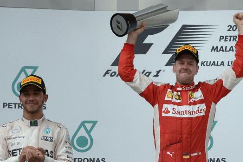 JUARA SEMULA: Pemandu Ferrari, Sebastian Vettel (kanan), meraikan kemenangannya di Grand Prix Malaysia sedang pesaing terdekat, Lewis Hamilton (kiri), terpaksa berpuas hati di tempat kedua. - Foto AFP