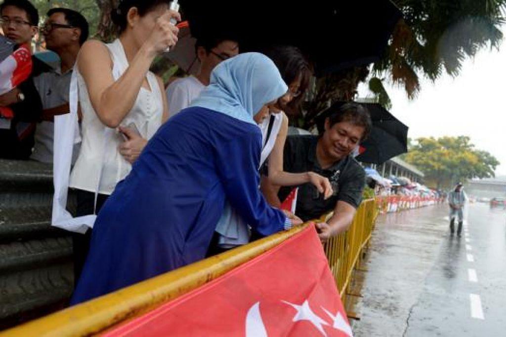 SEMANGAT PATRIOTIK: Cik Nur Hilyatun Nisaa bersama bapanya, Encik Ruslan Abedeen, bersemangat menggantung bendera Singapura di pagar yang disediakan di pinggir jalan Queensway. - Foto TUKIMAN WARJI