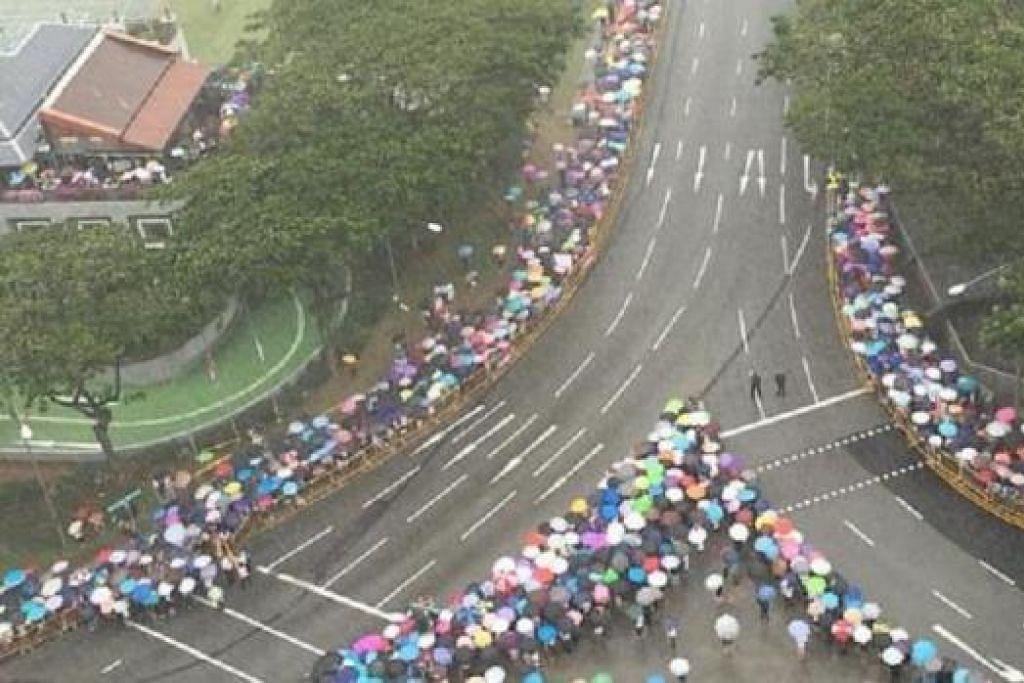 SEDIA MENANTI: Ribuan warga membarisi tepian jalan sambil menanti perarakan keranda mendiang Lee Kuan Yew yang dibawa keluar dari Bangunan Parlimen ke Pusat Budaya Universiti, Universiti Nasional Singapura, bagi acara persemadian negara. - Foto (ST)