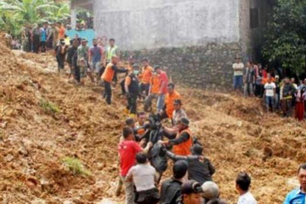 MEMINDAHKAN MAYAT: Anggota pasukan mencari dan menyelamat memindahkan mayat dari tapak tanah runtuh di perkampungan Tegal Panjang, Sukabumi, Jawa Barat. - Foto JAKARTA POST