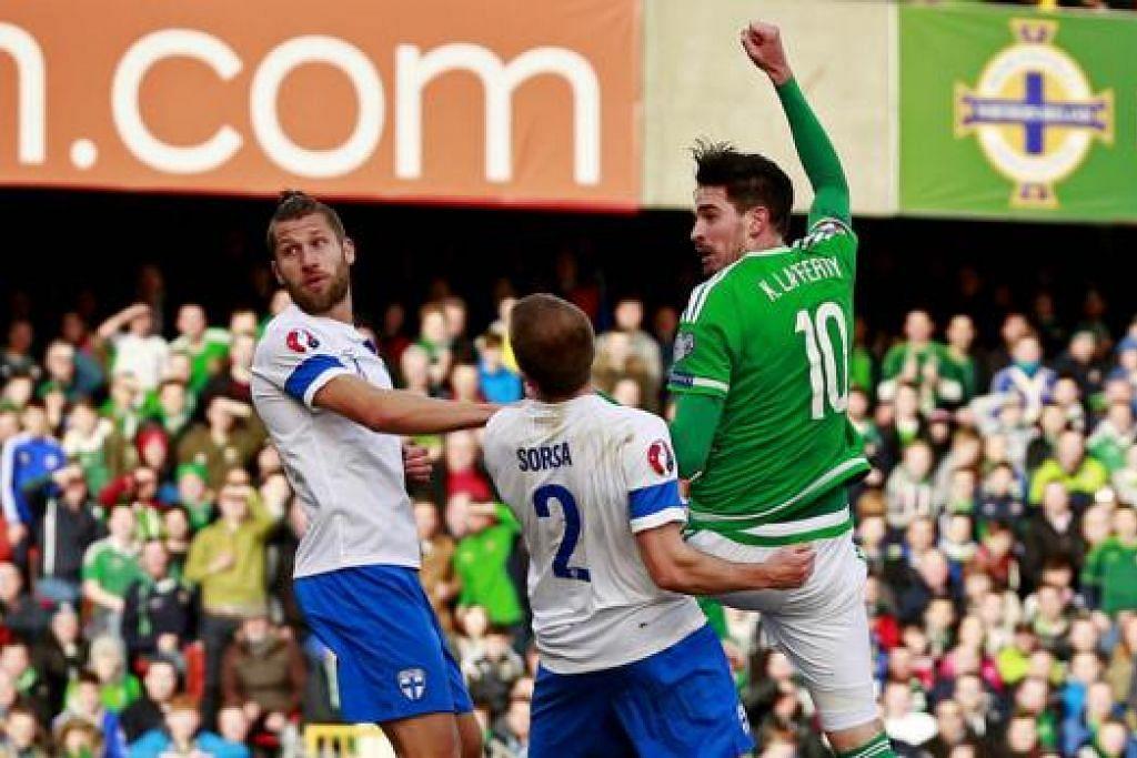 SENTUHAN CEMERLANG: Pemain Ireland Utara, Kyle Lafferty (jersi hijau), melepaskan percubaan cantik bagi gol kedua pasukannya semasa kemenangan ke atas Finland kelmarin. - Foto REUTERS