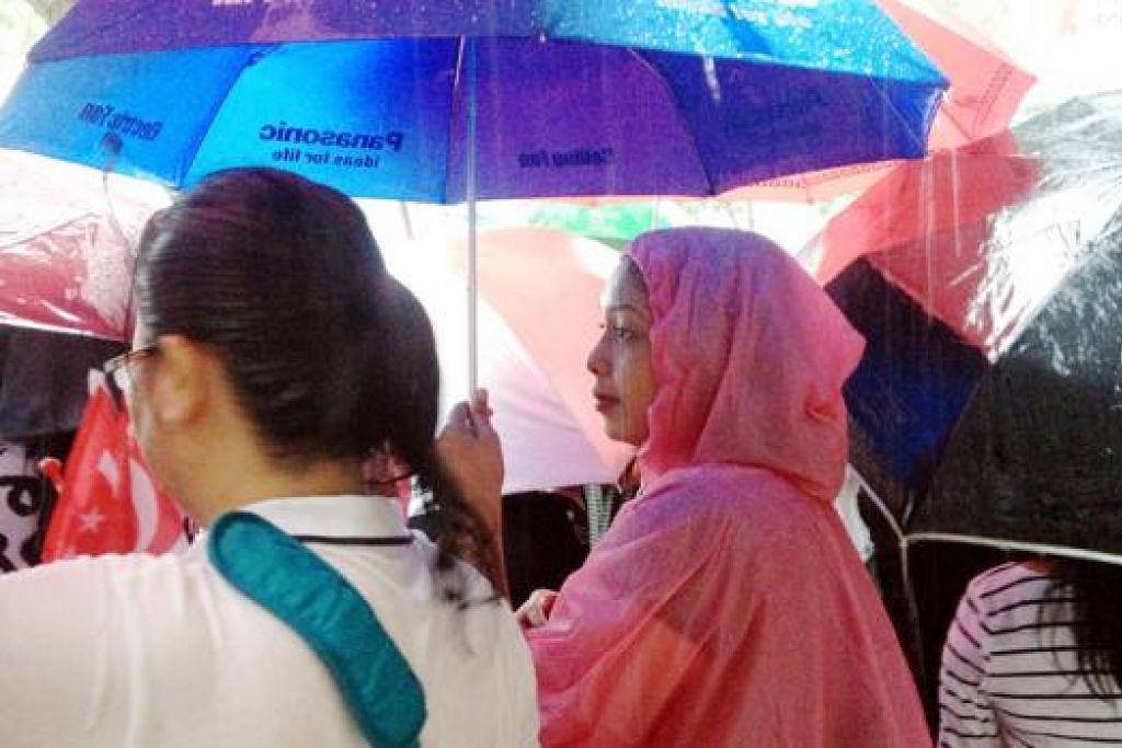 TIDAK BERGANJAK: Warga tetap berdiri di pinggir jalan untuk menyaksikan Perarakan Pengebumian Negara walaupun hujan turun dengan lebat sejak 10 pagi. - Foto ERVINA MOHD  JAMIL