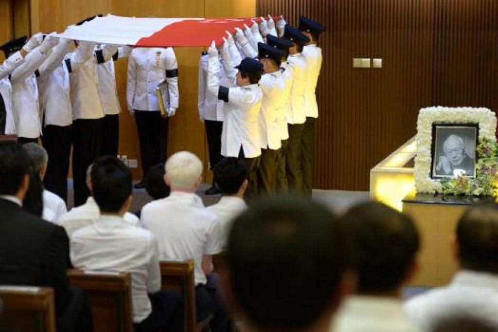 UPACARA PERSEMADIAN: Pasukan pengusung melipat bendera yang meliputi keranda mendiang Encik Lee. - Foto THE STRAITS TIMES