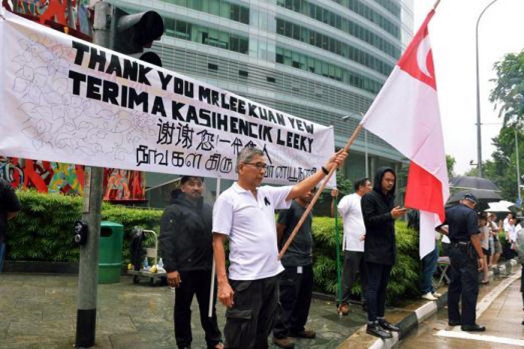 KIBAR BENDERA: Seorang warga mengibarkan bendera di pinggir jalan Raffles Quay sementara menunggu ketibaan Perarakan Pengebumian Negara. - Foto KHALID BABA