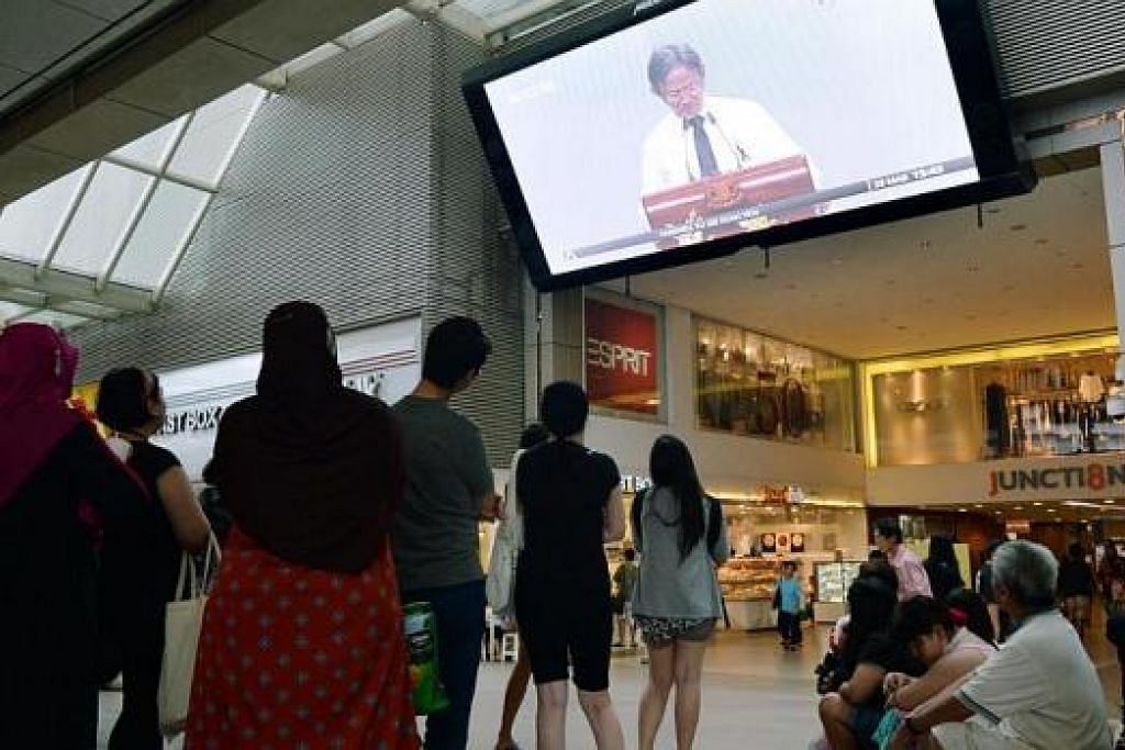 TURUT SAKSIKAN UPACARA: Orang ramai menyaksikan upacara Pengebumian Negara di UCC melalui televisyen di luar stesen MRT Bishan.