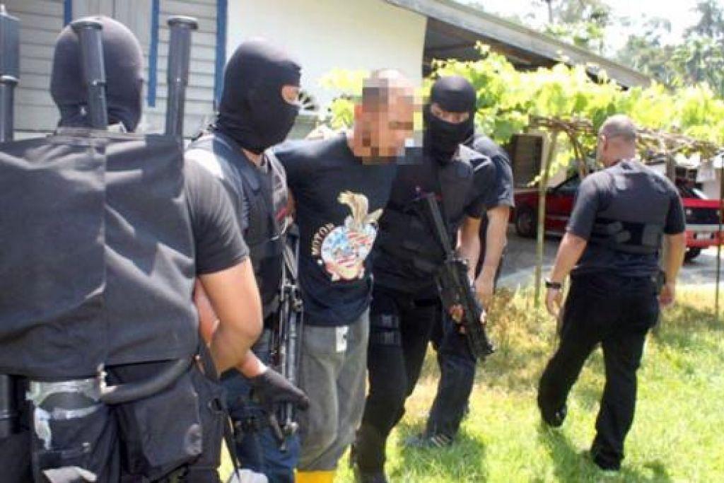 KEKANG PENGGANASAN: Pasukan pencegah pengganasan Malaysia memberkas seorang suspek yang disyaki terlibat dengan kumpulan militan di Iraq dan Syria. - Foto THE STAR
