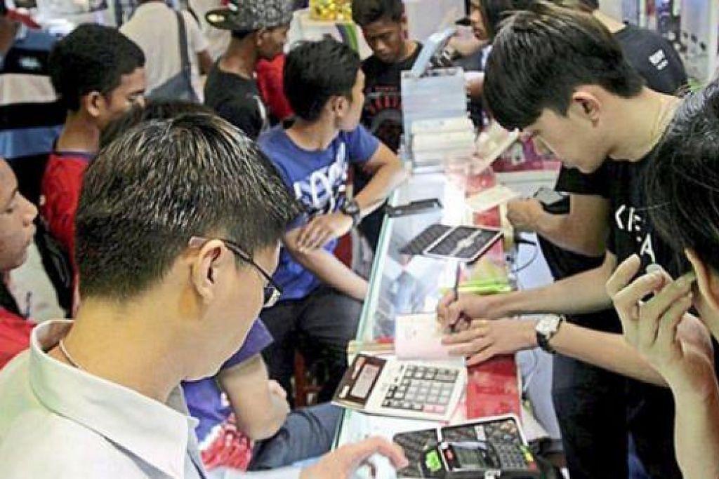 CUBA ELAK CUKAI: Para pembeli 'menyerbu' pusat beli-belah di Petaling Jaya untuk membeli telefon bijak dan peranti lain kerana percaya harga akan naik selepas GST dilaksana hari ini. - Foto THE STAR