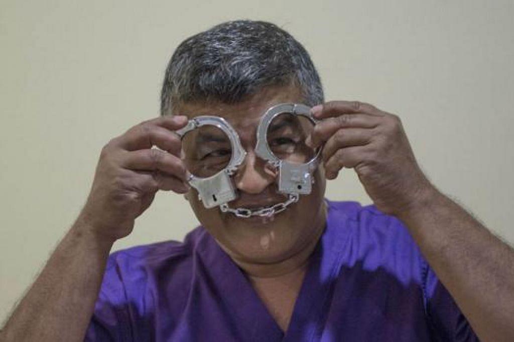 SENDA: Kartunis Malaysia Zulkiflee Anwar Ulhaque memakai baju penjara tiruan dan bergambar dengan gari di mahkamah semalam. - Foto AFP
