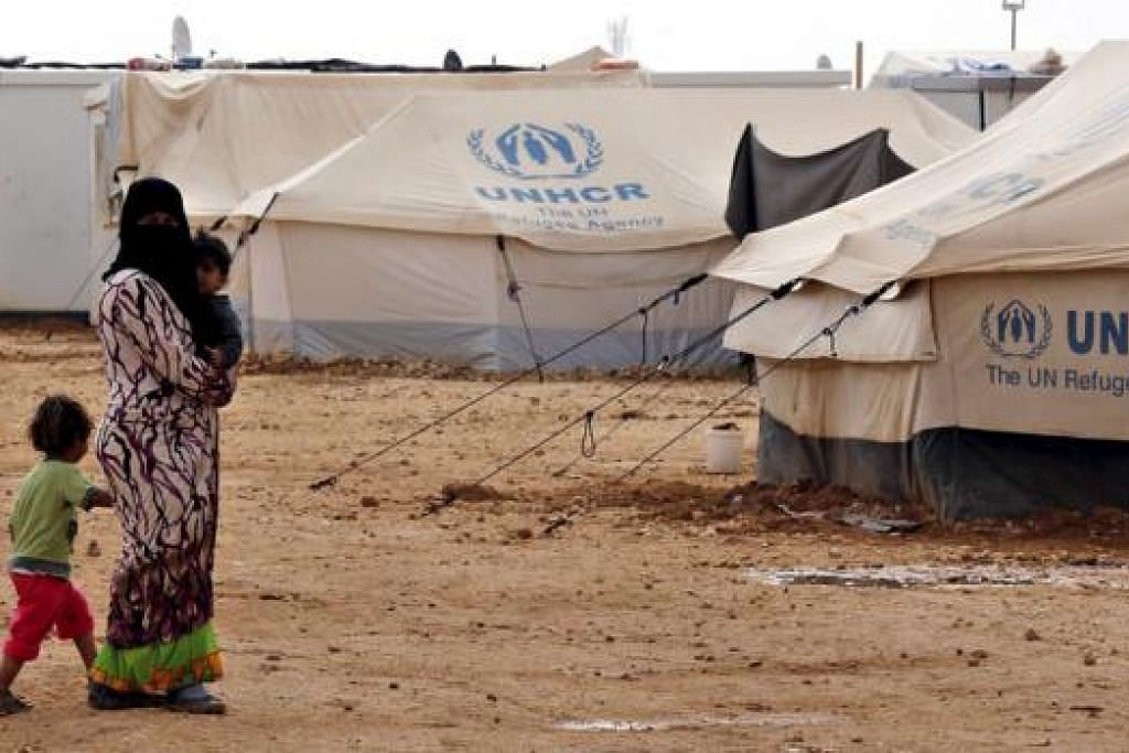 BANJIRAN PELARIAN: Seorang pelarian Syria bersama anaknya di Khemah pelarian Al Zaatari di Mafraq, sebuah bandar di Jordan, dekat sempadan Syria. - Foto REUTERS