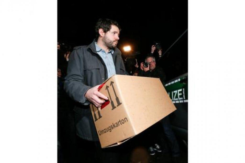 SIASATAN DITERUSKAN: (Atas) Penyiasat polis Jerman mengangkat kotak setelah menggeledah apartmen yang dipercayai milik juruterbang bersama pesawat Germanwings 4U9525, Andreas Lubitz, di Dusseldorf. - Foto-foto REUTERS