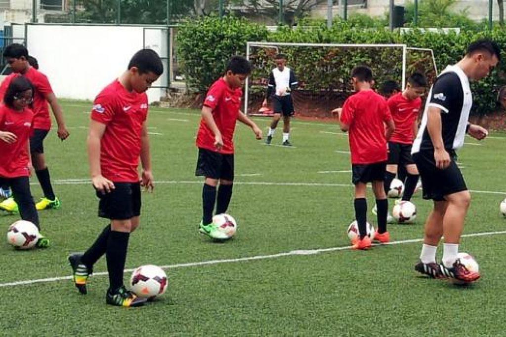 GIGIH ASAH BAKAT: Para pemain yang terdiri daripada pelajar sekolah rendah menjalani latihan di bawah projek perintis bola sepak akar umbi inisiatif Persatuan Bola Sepak Singapura (FAS) yang dilancarkan di padang Sekolah Rendah Sembawang pagi semalam.