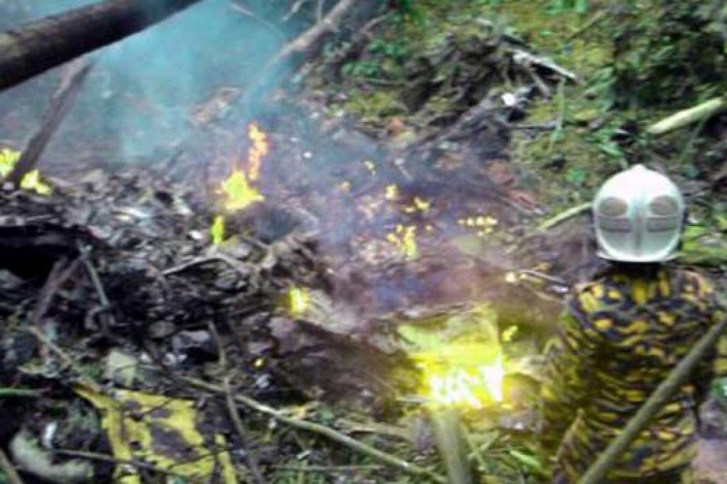 HANGUS: Bingkai-bingkai helikopter terbakar selepas terhempas di kawasan kebun getah di Kampung Sungai Pening, Semenyih, Selangor. - Foto BHM