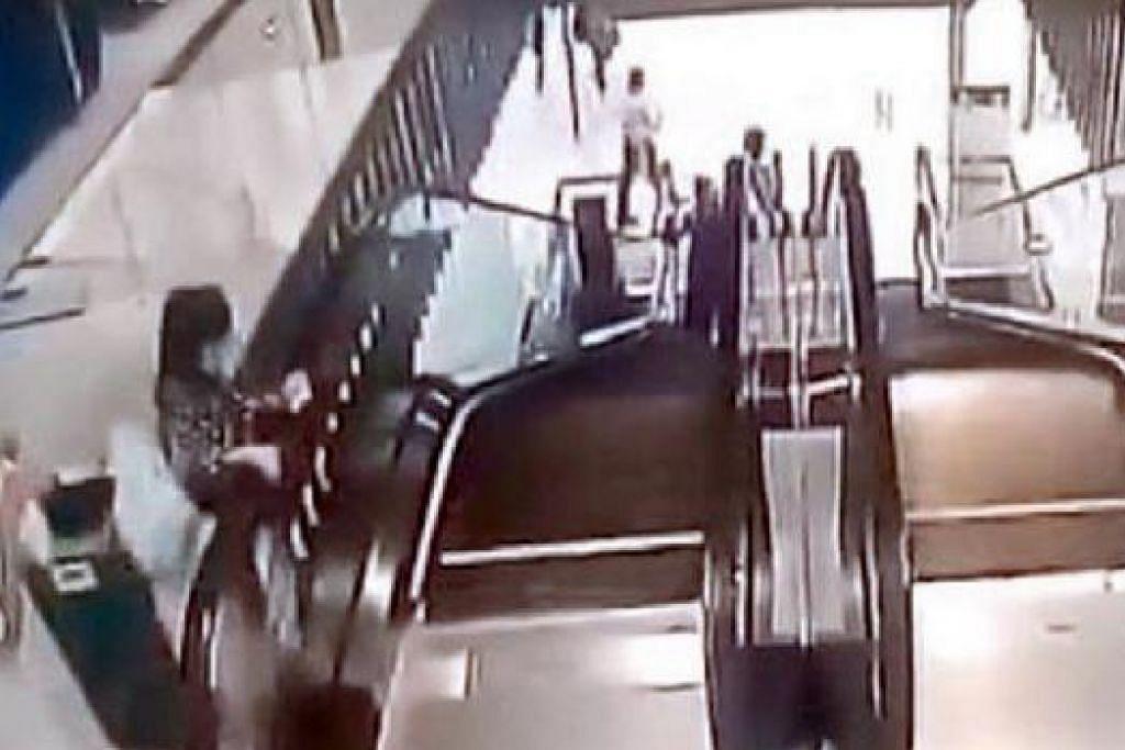 AKIBAT LALAI: Ibu yang asyik menggunakan telefon bimbit tidak sedar anaknya mengundang maut ketika bermain di tangga berjalan (gambar atas). Anak berusia enam tahun itu meninggal dunia selepas dia terjatuh dari tangga tersebut. - YOUTUBE.COM