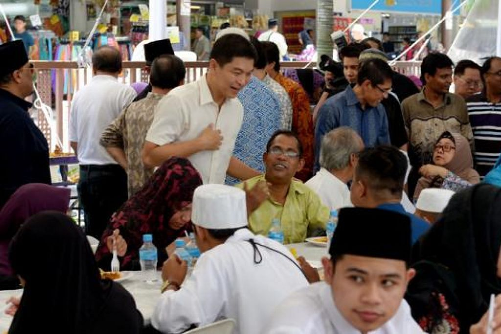 JAMUAN MASYARAKAT: Encik Tan (berbaju putih) beramah mesra dengan orang ramai yang menghadiri acara jamuan tengah hari masyarakat dekat Pasar Geylang Serai semalam. - Foto TUKIMAN WARJI
