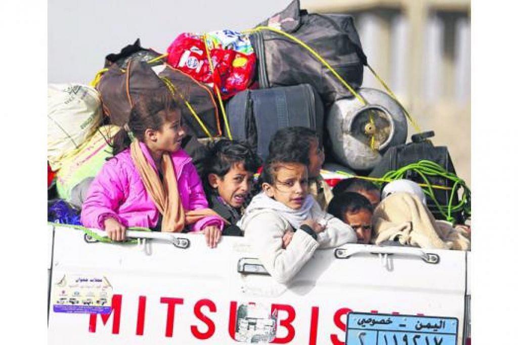 CARI TEMPAT PERLINDUNGAN: Kanak-kanak menaiki trak yang turut dimuatkan dengan beg-beg keluarga mereka yang melarikan diri dari Sanaa berikutan serangan udara yang dipimpin Arab Saudi. - Foto REUTERS
