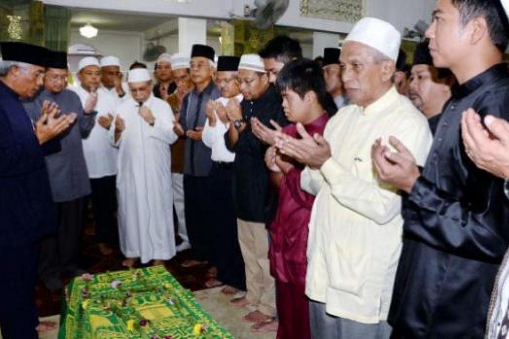 SOLAT JENAZAH DI MASJID BA'ALWIE: Imam Masjid Ba'alwie, Habib Hassan Al- Attas (berjubah putih), membaca doa selepas solat jenazah bagi Allahyarham Cikgu Mohamed Naim Daipi bersama-sama jemaah lain, termasuk (dari kiri) Encik Hawazi dan Dr Fatris. - Foto JOHARI RAHMAT