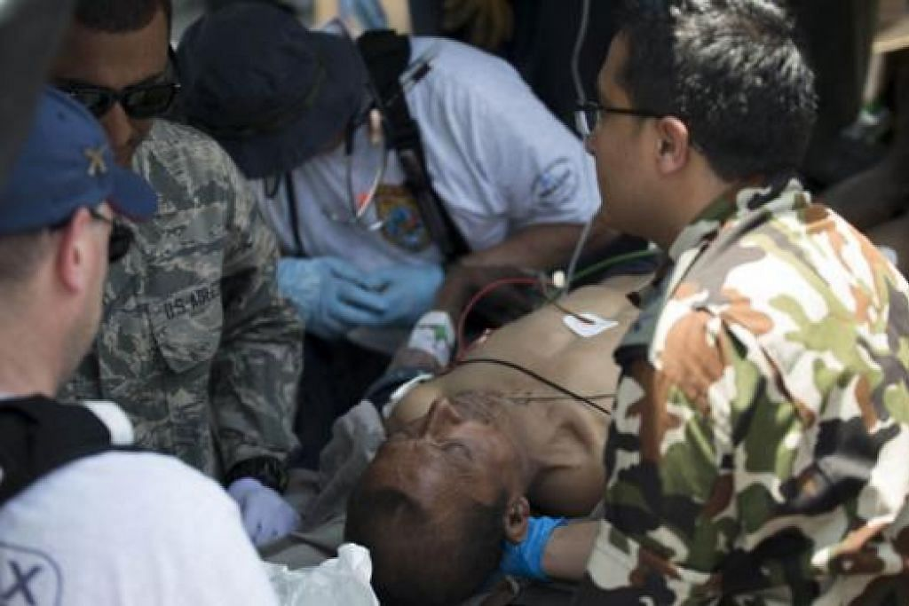 BERIKAN BANTUAN: Tentera Amerika dan tentera Nepal membantu seorang lelaki Nepal yang cedera semalam akibat gempa bumi terbaru yang melanda Nepal. - Foto AFP