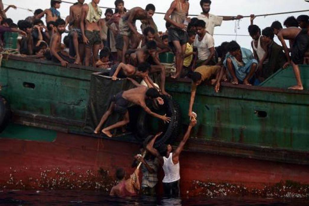 BERKONGSI MAKANAN: Pelarian Rohingya menghulurkan makanan yang digugurkan oleh heikopter tentera Thailand di selatan Pulau Koh Lipe, di Laut Andaman. - Foto AFP