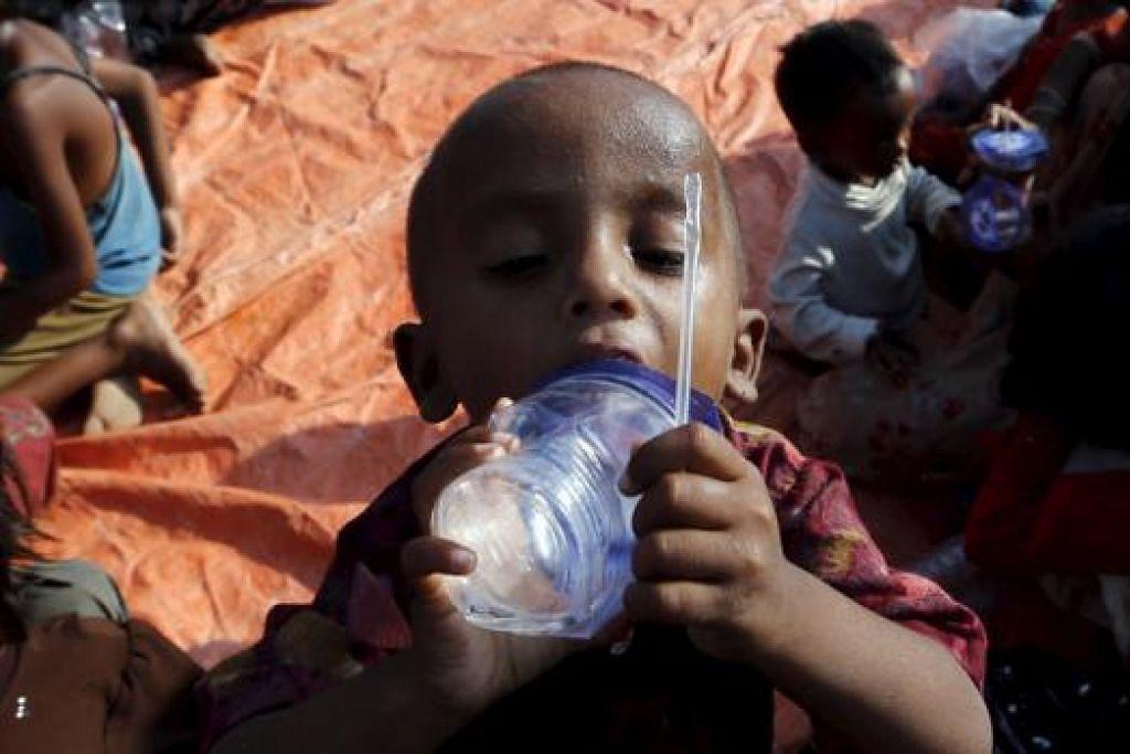 MINUM SETEGUK AIR: Kanak-kanak Rohingya ini meminum air setibanya dia di pelabuhan Julok, perkampungan Kuta Binje, Aceh, semalam. - Foto REUTERS