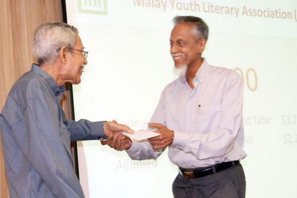 WAKAF DIAGIHKAN: Mantan Setiausaha Muis, Encik Syed Haroon Aljunied (kiri), meyampaikan wakaf berjumlah $6,000 kepada Presiden 4PM, Encik Izzuddin Taherally. - Foto JOHARI RAHMAT