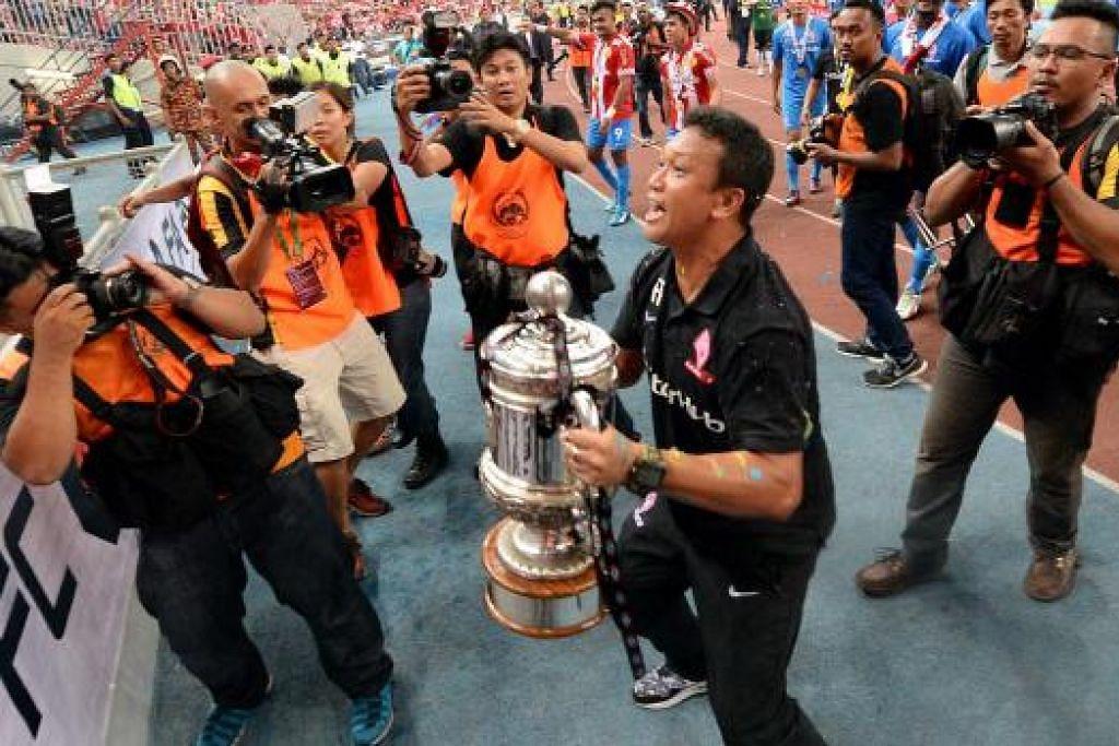 GIRANG: Fandi Ahmad meraikan piala pertama dalam pertandingan kalah mati yang dimenanginya.