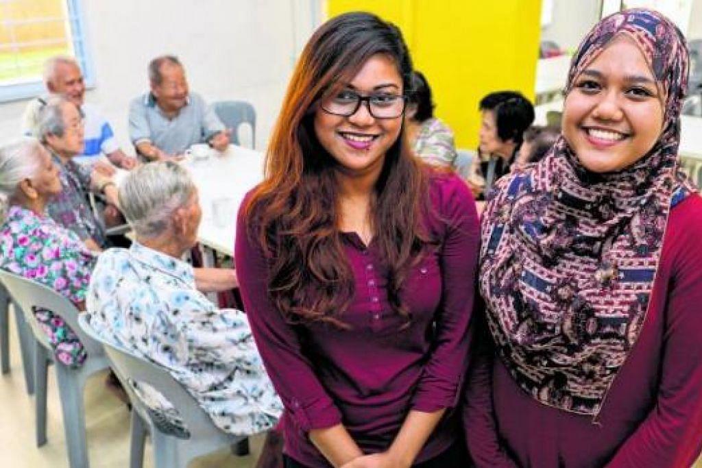 HATI TERTARIK PADA WARGA EMAS: Cik Nabilah Anuar (kanan), 19 tahun; dan Cik Norshaqilah Zabah, 20 tahun, di Pusat Kegiatan Warga Tua (SAC) di Blok 123, Ang Mo Kio. - Foto M.O. SALLEH
