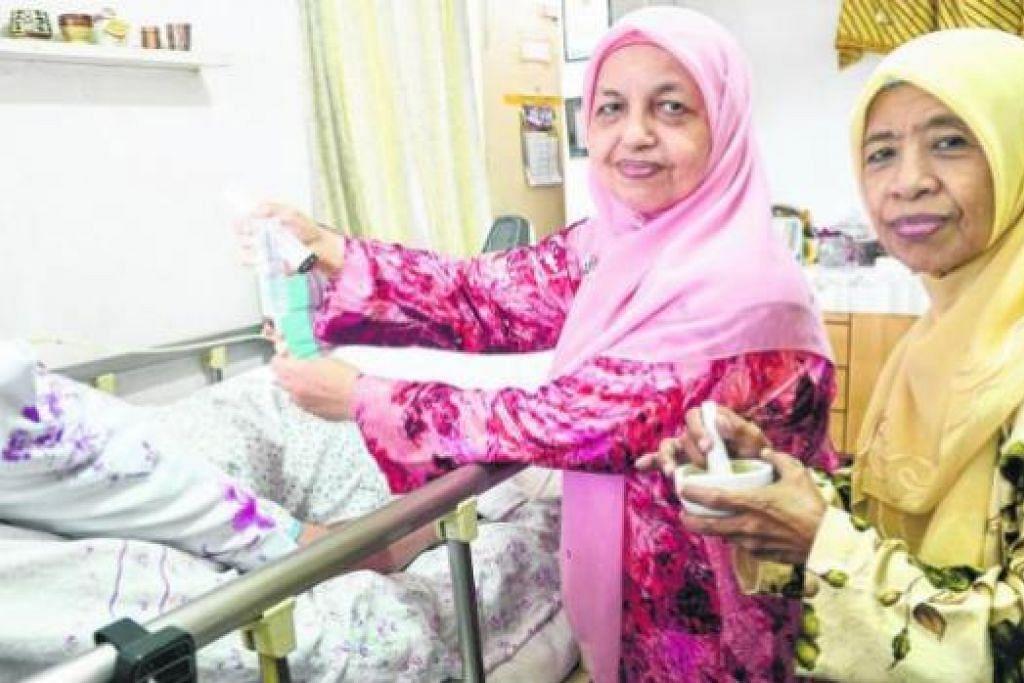 SUKA MEMBANTU WARGA TUA SEJAK MUDA: Cik Kalsom Hamid (kiri), 65 tahun, memberi susu kepada wanita berpenyakit angin ahmar (terselindung) berusia 80 tahun yang dijaga di rumahnya, diperhatikan oleh jiran yang juga selalu dihantarnya ke hospital, Cik Siti Buang, 72 tahun, yang menghidap barah usus. - Foto JOHARI RAHMAT