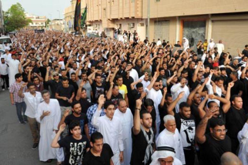 ADAKAN BANTAHAN: Penduduk Qatif, 400 kilometer ke timur Riyadh, yang kebanyakannya penganut Syiah, mengadakan bantahan selepas penyerang berani mati meletupkan bom di sebuah masjid di sebuah kampung di wilayah itu Jumaat lalu hingga mengorbankan 21 jemaah. - Foto AFP