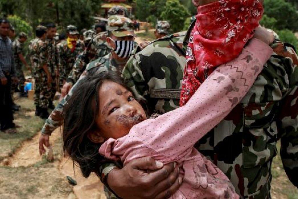 BENCANA ALAM: Seorang kanak-kanak perempuan yang cedera didukung seorang anggota tentera di Sindhupalchowk untuk mendapatkan rawatan menyusuli gempa bumi di Nepal yang berlaku pada 28 April lalu. - Foto REUTERS