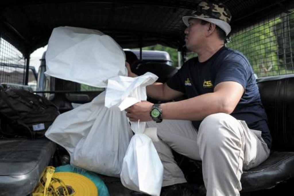KUMPUL BUKTI: Seorang pegawai polis Malaysia membawa bungkusan berisi sisa mayat manusia yang ditemui di dalam sebuah kubur besar di khemah tahanan di Wang Kelian dekat sempadan Malaysia-Thailand, kelmarin. - Foto AFP