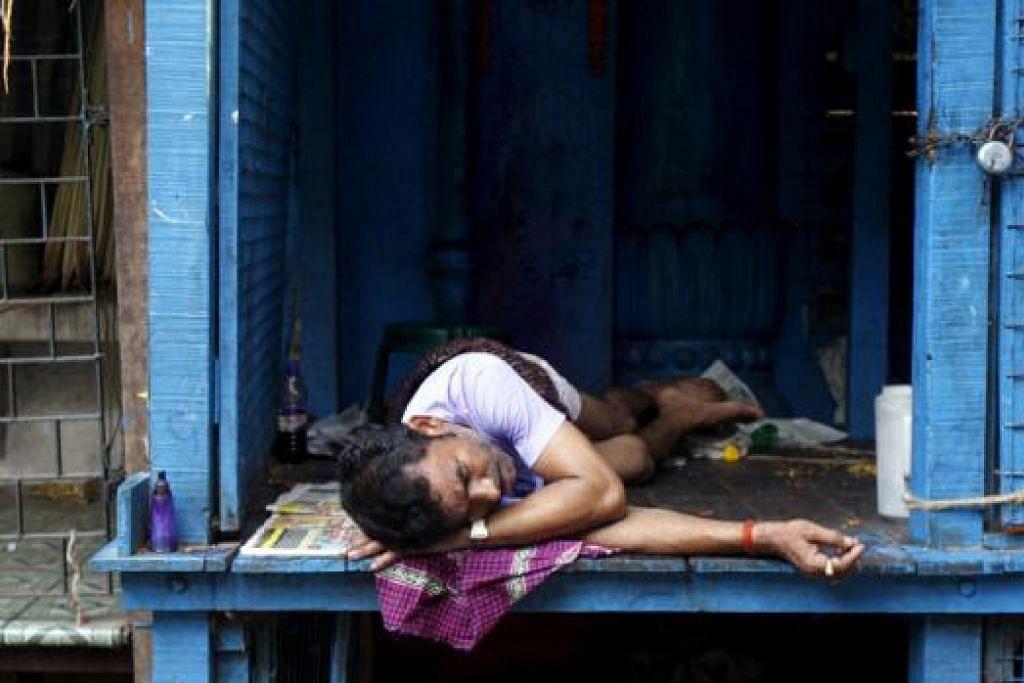 LETIH DEK PANAS: Seorang penjual bunga tertidur di sebuah pasar di Kolkata yang mengalami suhu panas mencecah 37 darjah Celsius. - Foto REUTERS