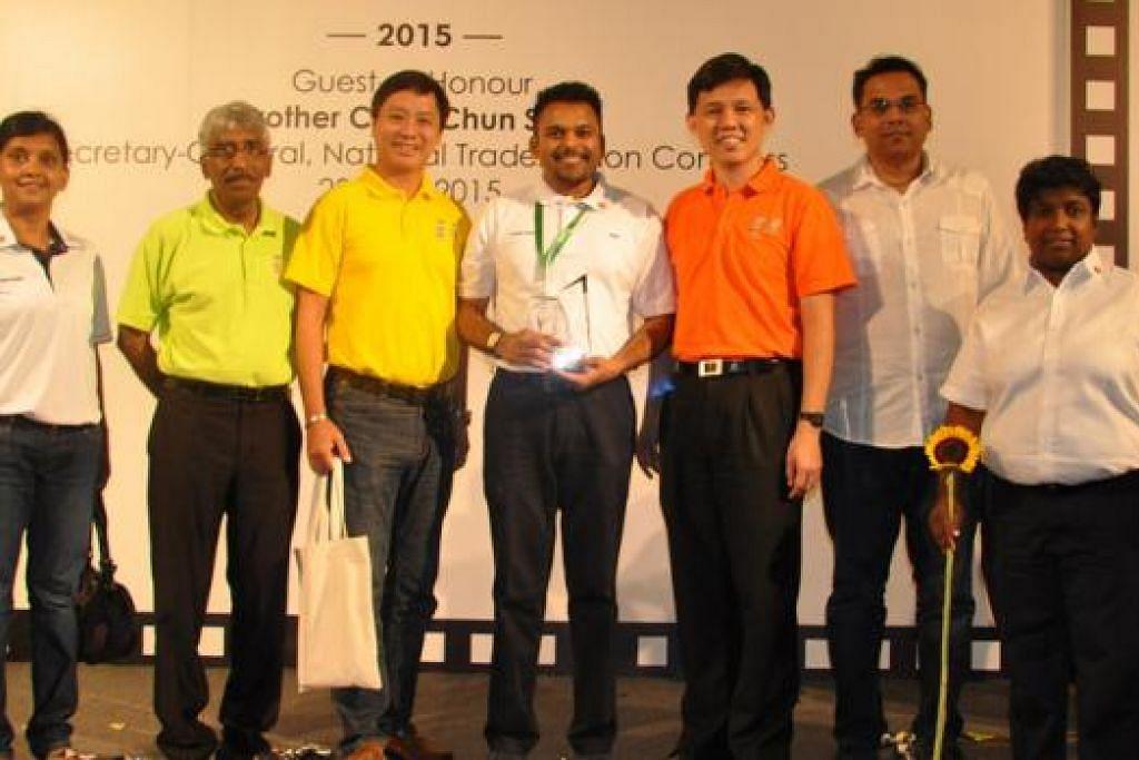 MENYOKONG USAHA PERTINGKAT DAYA PENGHASILAN: Encik Abdul Aziz Yusof (memegang trofi) bersama Encik Chan Chun Sing (berbaju oren) dalam majlis penyampaian anugerah anjuran Kongres Kesatuan Sekerja Kebangsaan (NTUC) baru-baru ini. - Foto CLEANING EXPRESS