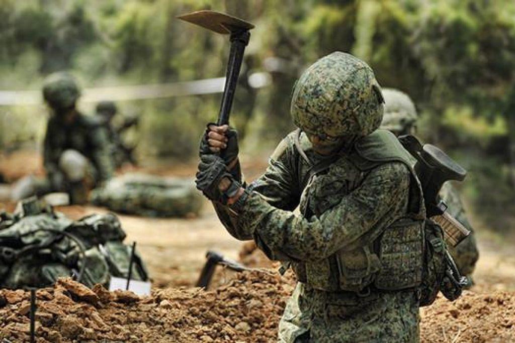 GALI PARIT: Seorang askar menggunakan cangkul untuk menggali parit dalam satu latihan di kawasan hutan. - Foto-foto MINDEF