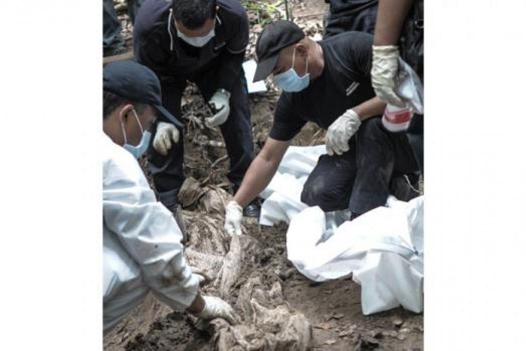 SISA MAYAT: Anggota pasukan forensik Polis Diraja Malaysia menggali kubur yang ditemui di kawasan kem pendatang asing di Bukit Wang Burma, Perlis. - Foto AFP